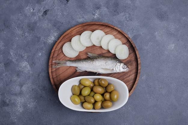 Aceitunas en escabeche, pescado y rodajas de cebolla en placa de madera.