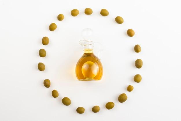 Aceitunas en forma de círculo que rodea la botella de aceite de oliva