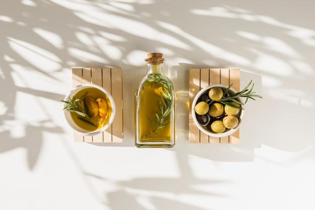 Aceitunas frescas con botella de aceite en el fondo blanco