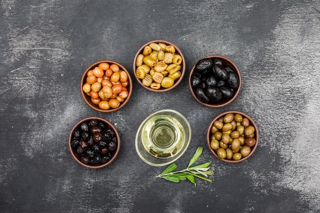 Aceitunas marinadas y aceite de oliva en cuencos de arcilla y frasco de vidrio con vista superior de rama de olivo en grunge gris oscuro