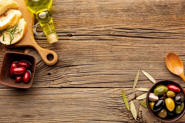 Aceitunas mezclan pan y cuchara de madera con espacio de copia