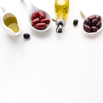Aceitunas moradas rojas en cucharas con botellas de aceite