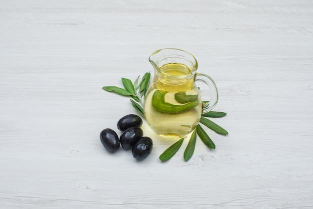 Aceitunas negras y aceite de oliva en un frasco de vidrio con hojas de olivo vista lateral sobre tablón de madera blanca