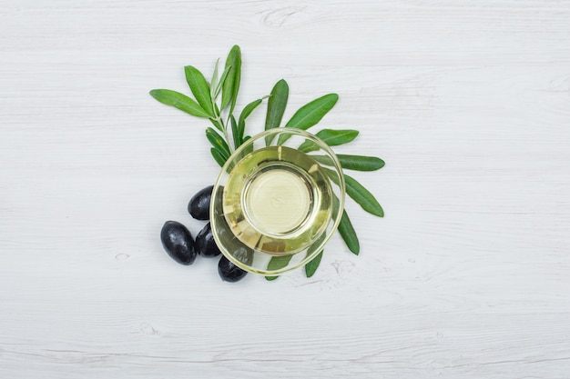 Aceitunas negras y aceite de oliva en una lata de vidrio con vista superior de hojas de olivo sobre tablón de madera blanca