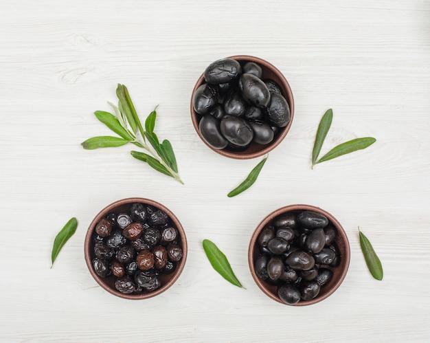 Aceitunas negras y marrones en cuencos de arcilla con rama de olivo y hojas vista superior en madera blanca