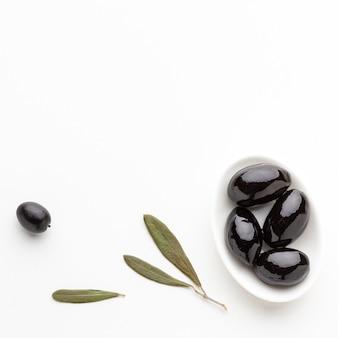 Aceitunas negras planas en un plato con hojas con espacio de copia