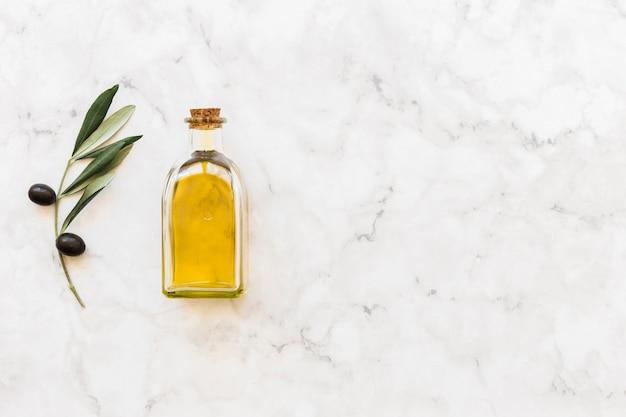 Aceitunas negras con ramita y botella de aceite en el fondo de mármol blanco