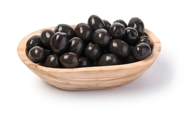 Aceitunas negras en tazón de madera aislado en blanco