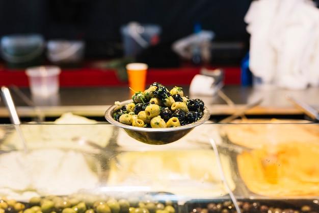 Aceitunas negras y verdes en el tazón en mostrador de vidrio