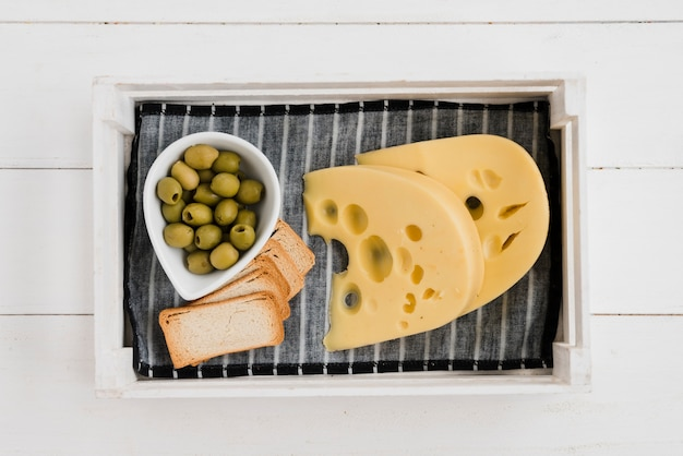 Aceitunas con pan tostado y queso maasdam en servilleta en bandeja sobre el escritorio de madera
