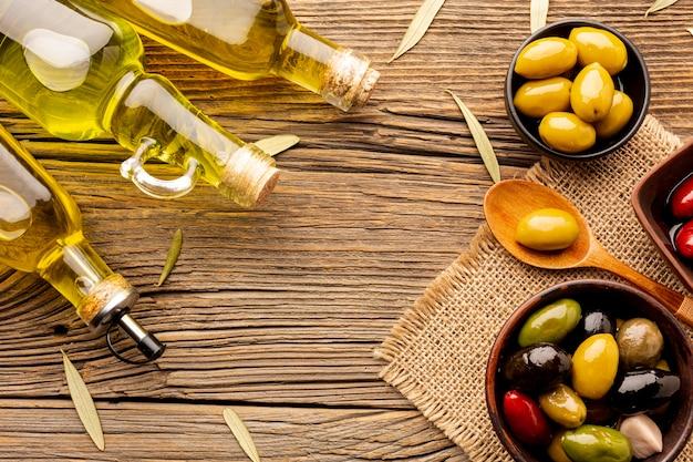 Aceitunas planas en cuencos, botellas de aceite y hojas sobre material textil