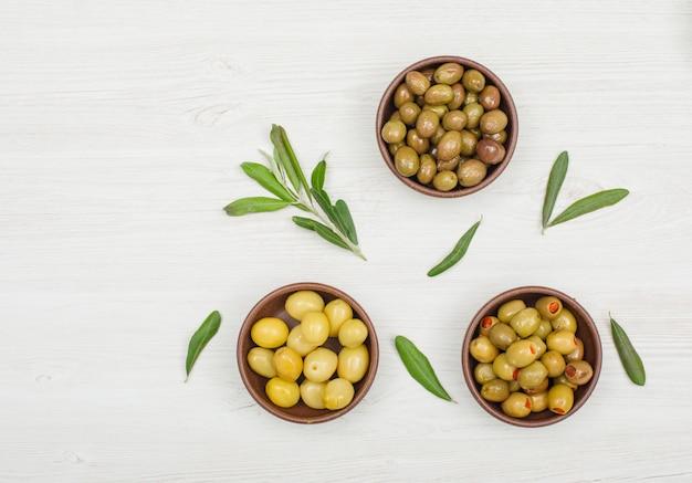 Aceitunas surtidas en cuencos de arcilla con rama de olivo y vista superior de hojas en madera blanca