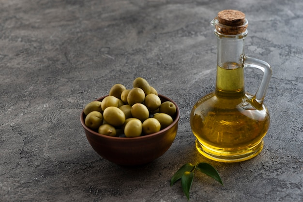 Aceitunas en un tazón y botella de aceite cercana