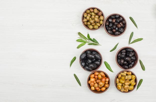 Aceitunas variadas con hojas de olivo en cuencos de arcilla sobre madera blanca, plana.