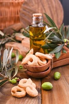 Aceitunas verdes en latas con hogaza de pan fresco y rama de aceitunas jóvenes, botella de aceite de oliva