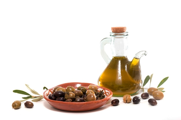 Aceitunas verdes y negras con botella de aceite de oliva.