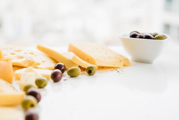 Aceitunas verdes con rodajas de queso sobre el escritorio blanco