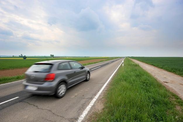 Acelere la carretera de asfalto automático a través del campo verde y las nubes en el cielo azul en día de verano