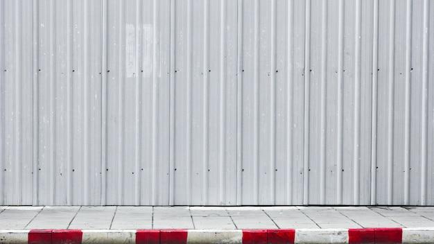 Acera y bordillo rojo-blanco con pared de metal corrugado.