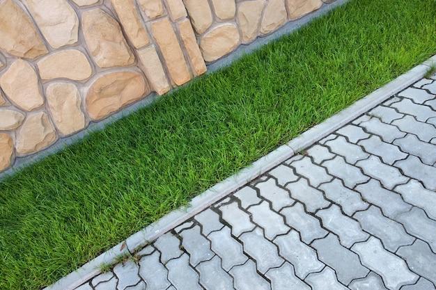 Acera pavimentada con ladrillos de cemento y césped con pasto verde
