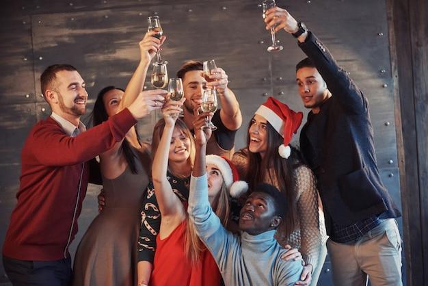 ¡se acerca el año nuevo! grupo de alegres jóvenes multiétnicos con sombreros de santa en la fiesta, posando el concepto de gente de estilo de vida emocional
