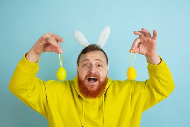Se acerca la búsqueda de huevos. hombre caucásico como un conejito de pascua con ropa casual brillante sobre fondo azul de estudio. felices saludos de pascua. concepto de emociones humanas, expresión facial, vacaciones. copyspace.