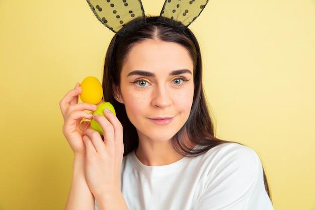 Se acerca la búsqueda de huevos. mujer caucásica como un conejito de pascua sobre fondo amarillo de estudio. felices saludos de pascua. modelo de mujer hermosa. concepto de emociones humanas, expresión facial, vacaciones. copyspace.