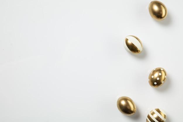 Se acerca la búsqueda de huevos, tradiciones de pascua, huevos de color dorado, fondo de vista superior