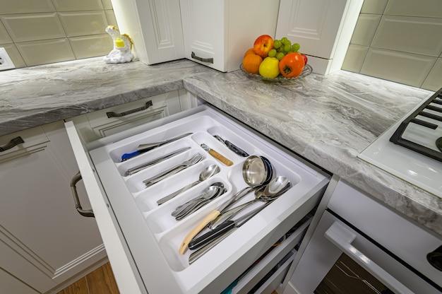 Acercamiento para abrir los cajones en el interior de la cocina clásica moderna blanca con muebles de madera, algunos cajones están abiertos