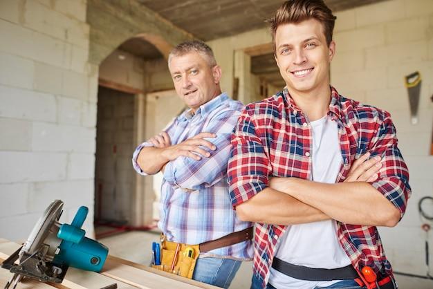 Acercamiento al carpintero experimentado y a su empleado más joven