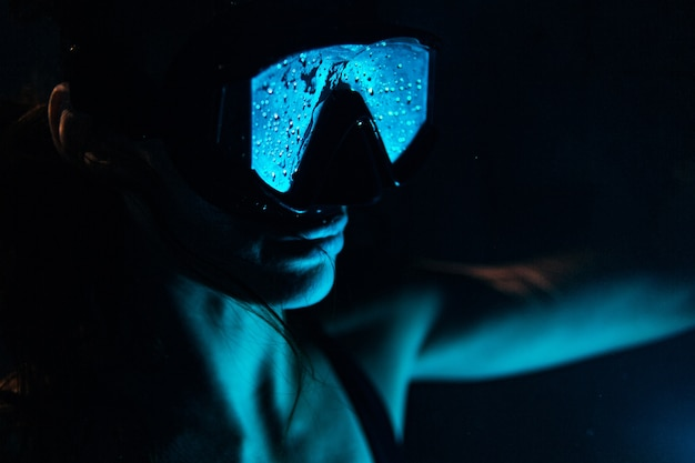 Acercamiento de la hermosa mujer en el agua de la piscina con máscara de natación