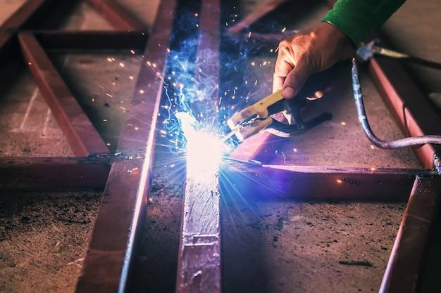 Acercamiento a mano de soldadura de acero con chispa.