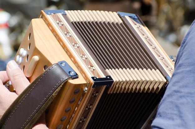 Acercamiento de una persona sosteniendo y tocando el acordeón