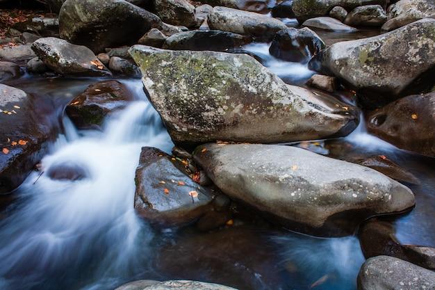 Acercamiento de las rocas en el flujo en cascada del río en un día frío