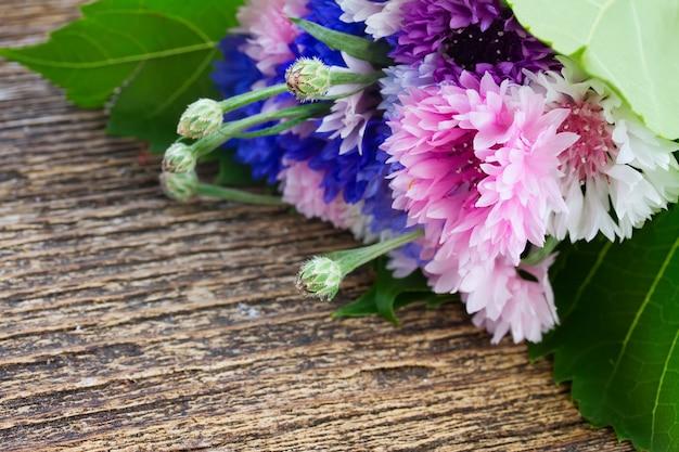 Acianos azules y rosas en mesa de madera
