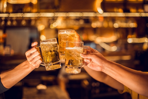 ¡aclamaciones! grupo, jarra de cerveza, hombres jóvenes preparan vasos de cerveza para celebrar su éxito.