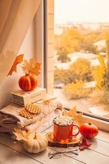 Acogedor bodegón otoñal en el alféizar de la ventana: cálidos suéteres de lana, calabazas, hojas de arce y una taza de chocolate con malvaviscos.