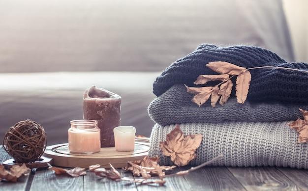 Acogedor bodegón otoñal con velas y un suéter