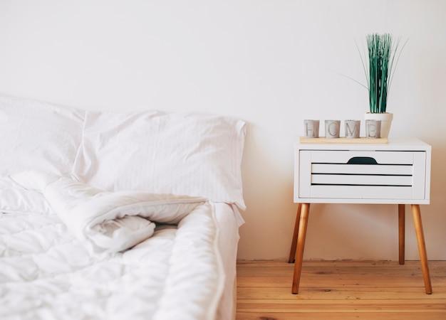 Acogedor dormitorio en color blanco con mesita de noche.