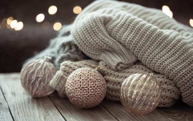 Acogedor fondo navideño con adornos navideños y elemento tejido sobre un fondo borroso.