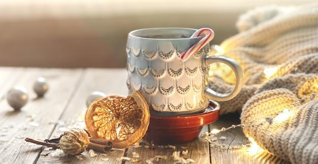 Acogedor fondo navideño con una taza, elemento de punto, estado de ánimo invernal, comodidad en el hogar.
