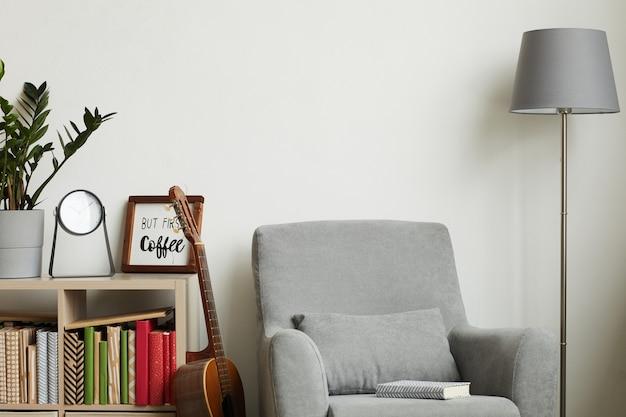 Acogedor interior moderno con elementos de decoración mínimos y sillón gris contra la pared blanca