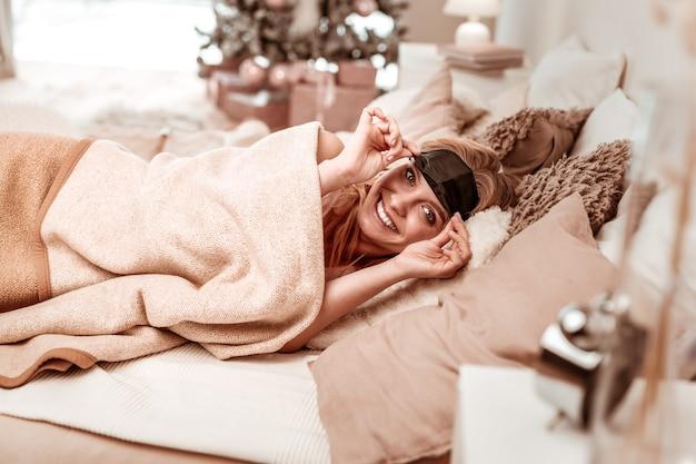En acogedor mal. mujer radiante activa levantando su máscara para dormir mientras se despierta de un sueño profundo