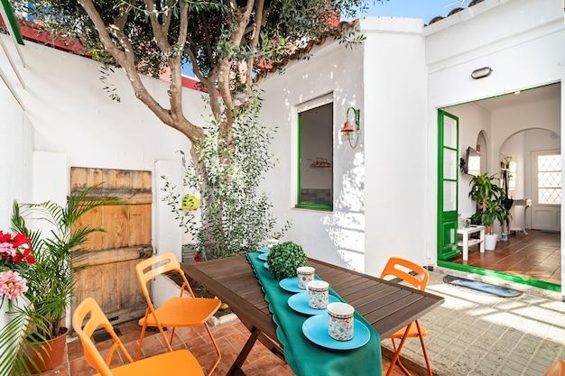Acogedor patio con árboles y mesa servido con tazas de té.