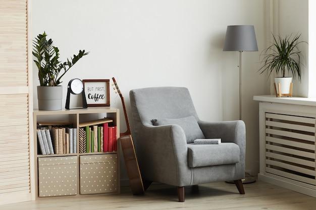 Acogedor rincón de lectura en un interior moderno y minimalista, se centra en el sillón gris contra la pared blanca