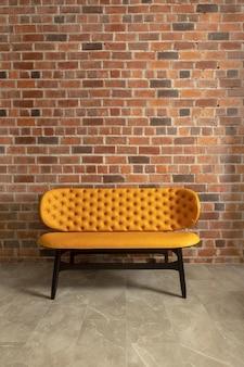 Acogedor sofá moderno junto a la pared de ladrillo