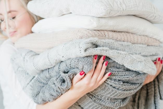 Acogedor textil para el hogar de invierno. mujer con manta tejida y pila de almohada.