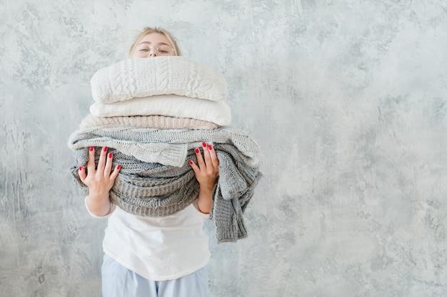 Acogedor textil para el hogar. mujer con manta tejida caliente y pila de almohada.