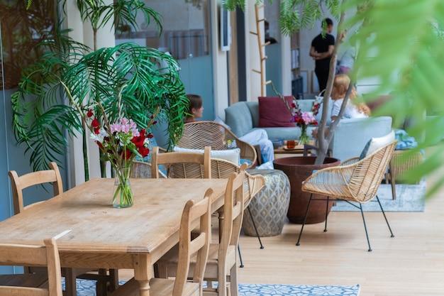 Acogedora cafetería en el hotel decorada con plantas verdes y flores.