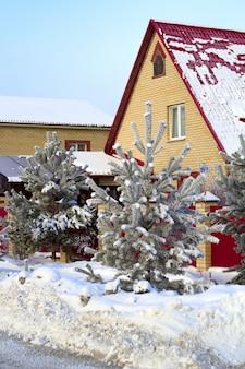 Acogedora calle con casas de ladrillo en invierno con árboles nevados.